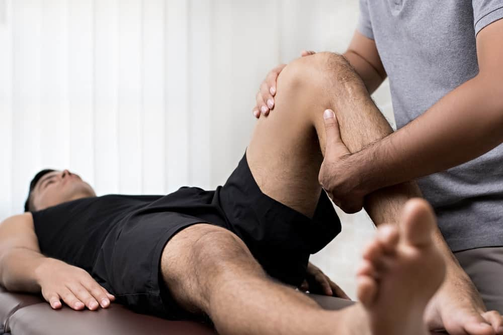 chiropractor-adjusting-male-patient-leg