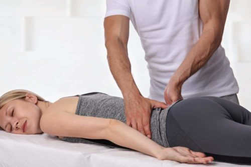 male-chiropractor-adjusting-lower-back-female-patient