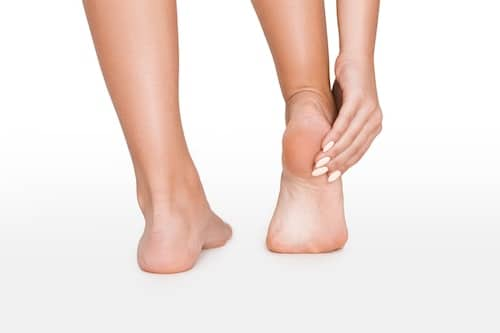 Young woman touching her painful sole, isolated on white, plantar fasciitis