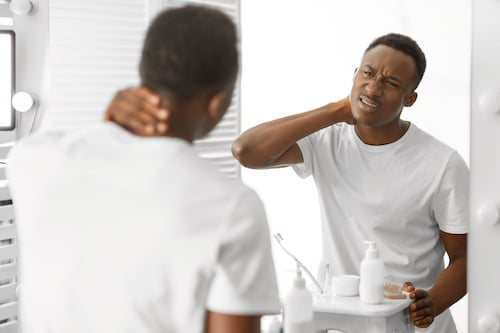 African Man Touching Aching Neck Suffering From Pain In The Morning, Standing Near Mirror In Bathroom At Home. Male Health Problems, Cervicalgia, Poor Posture And Headache Issue. Selective Focus