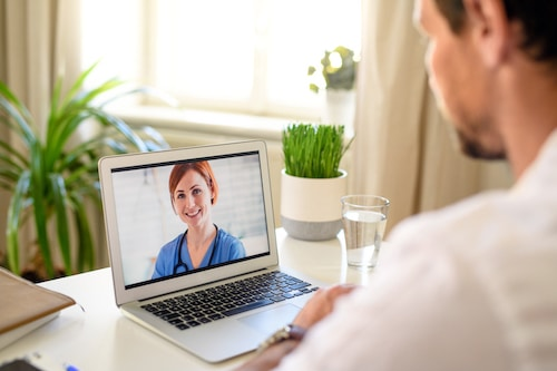 Mature man having video call with doctor on laptop at home, online consultation concept.
