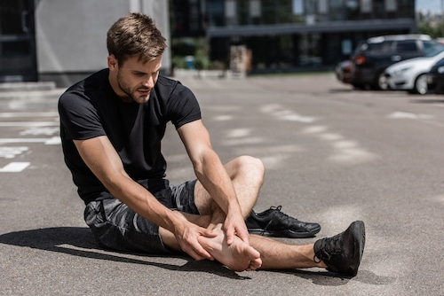 muscular bearded barefoot sportsman with foot pain on street