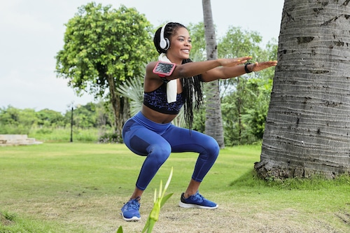Happy beautiful young Black sportwoman in headphones doing squats in park after morning run