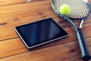 close up of tennis racket with ball and tablet pc