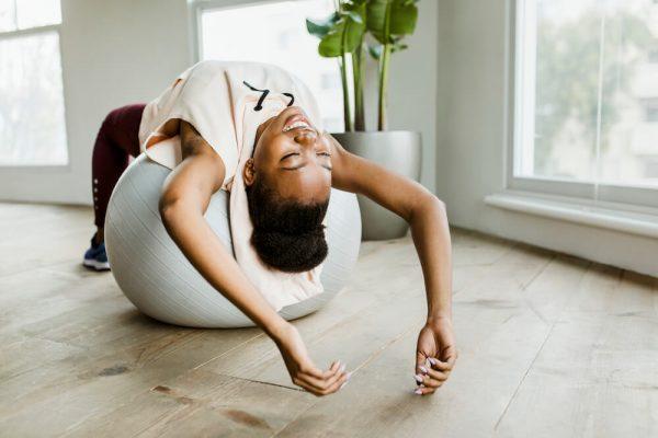black-woman-doing-stretching-back-spasm-on-a-balance-ball