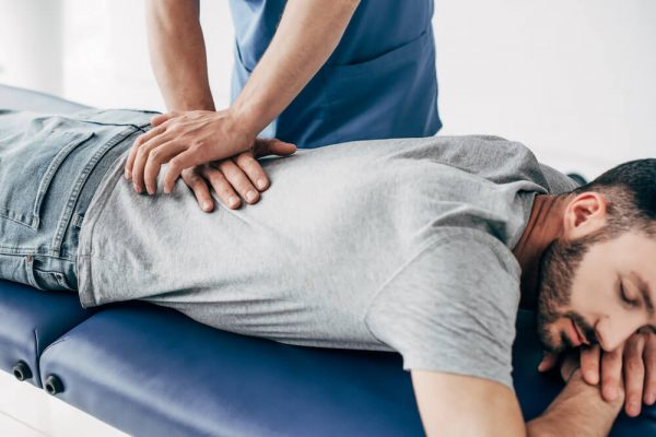 chiropractor-massaging-back-spasm-of-man-on-massage-table