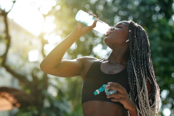 fit-woman-drinking-water-to-relieve-back-spasms