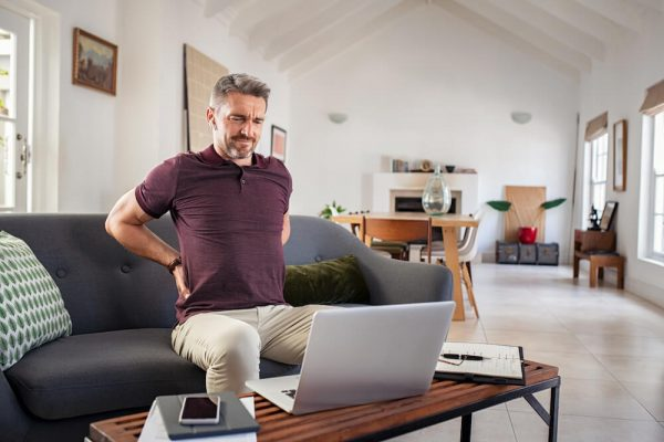 mature-man-stretching-back-spasm-while-working-at-home